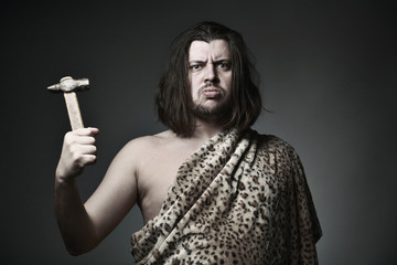 Wild man wearing leopard skin hold old hammer.