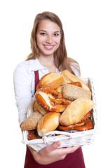 Blonde Bäckereiverkäuferin zeigt Brotkorb