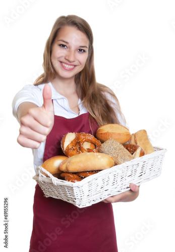 Leinwanddruck Bild Blonde Bäckereiverkäuferin zeigt den Daumen hoch