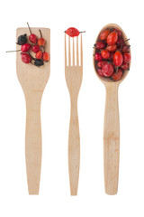 Wooden spoon, fork, paddle with  rosehips