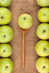 Spoon with green apple lying on the sackcloth among green apples