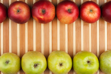 Green and red apples lie on the bamboo mat