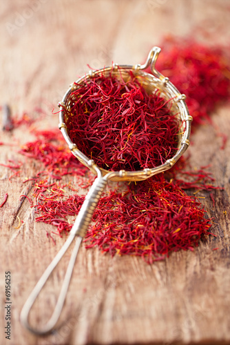 Leinwandbild Motiv saffron spice in rustic sieve on old wooden background, closeup