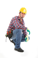 A construction worker squats down and serious