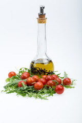 Heap of ruccola, tomatoes and olive oil with the thyme