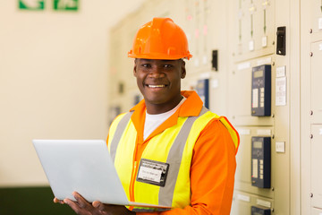 african engineer holding laptop in power plant control room