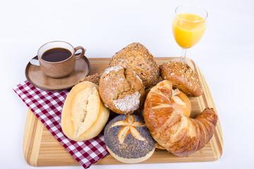 Viele Brötchen auf Brett mit Kaffee und Orangensaft
