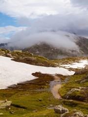 Thin footpath in snowy autumn meadows of high Alpine mountains