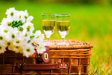 basket with daisies and glasses with champagne