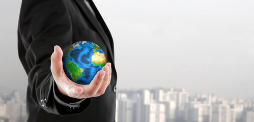 Business man holding the small world in his hand (Elements of th