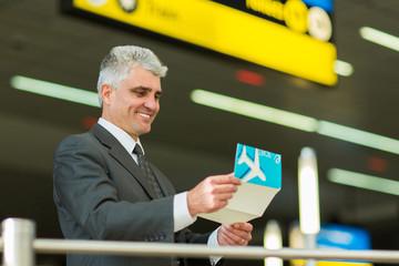senior businessman looking at his air ticket