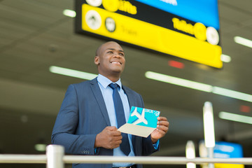 young african businessman holding air ticket