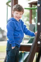 Gorgeous little boy playing in play ground.