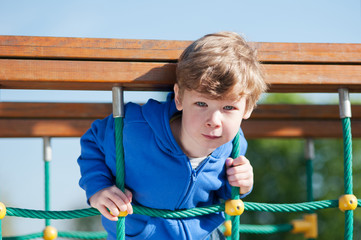 Boy in the park, playing on playground equipment.
