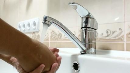 Woman washing her hands in bathroom sink