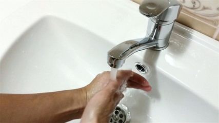 Woman washing her hands in bathroom sink