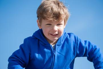 Boy wearing a blue fleece top against a clear blue sky