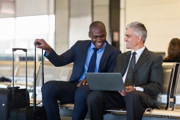 businessmen using laptop computer at airport