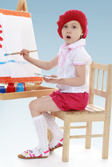 young artist paint brush on the easel.