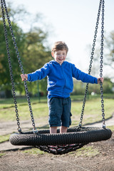 Toddler boy playing on a really big swing.