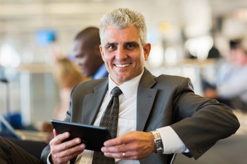 businessman holding tablet computer at airport