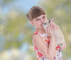 Charming girl kisses rabbit.