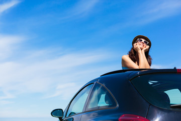 Relaxed woman on summer vacation leaning out sunroof
