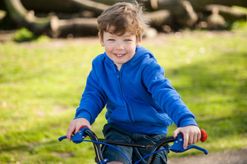 Smiling happy boy on his bicycle.