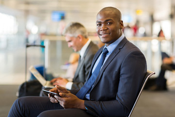 african business traveller using tablet pc at airport