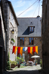 Courtyard of medieval architecture, flags of Dinan