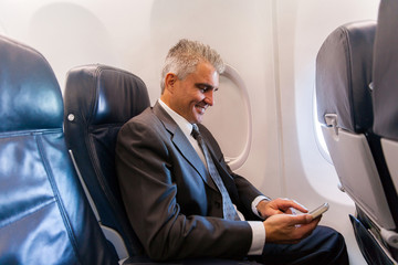 middle aged businessman using cell phone on airplane