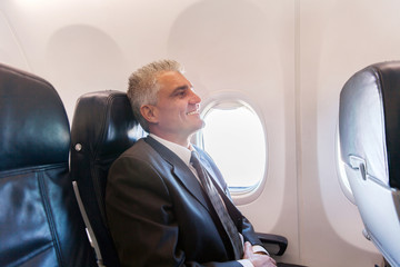 middle aged airplane passenger relaxing on air plane