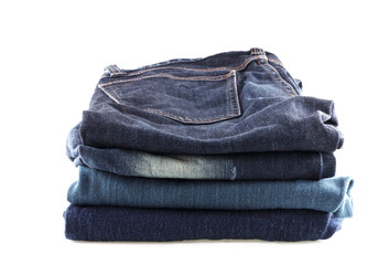 Many jeans stacked isolated  on a white background