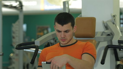 young man looks through a training program on the tablet