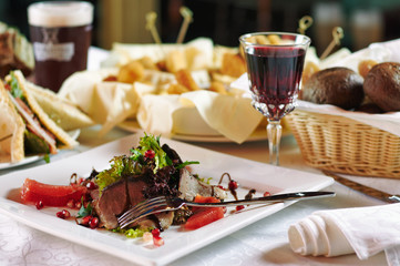 Meat salad on plate and glass of wine