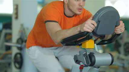 young man doing exercise for the legs on a stationary bike