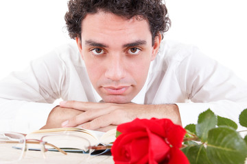 Man relaxing with flower and good book with glasses aside