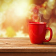 Red coffee cup over autumn background