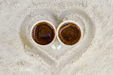 two cups with hot coffee on sand