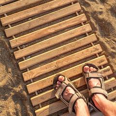man feet on beach sand
