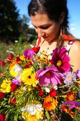 Jeune fllle cueillant  un bouquet de fleurs des champs