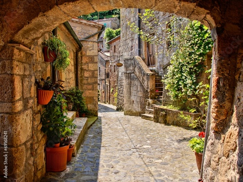 Arched cobblestone street in a Tuscan village, Italy 69168241