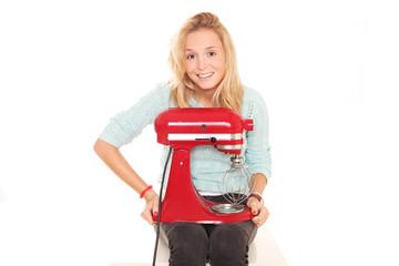 junge Frau hat Küchenmaschine auf ihrem Schoß