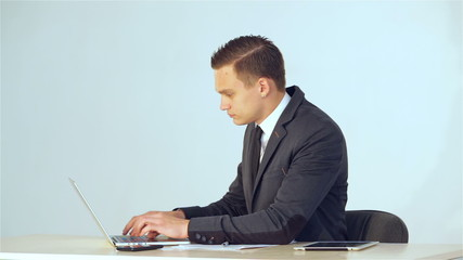 young businessman off the laptop and smiling at the camera