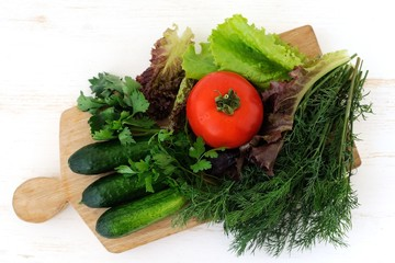 Green cucumbers, tomato and fresh herbs