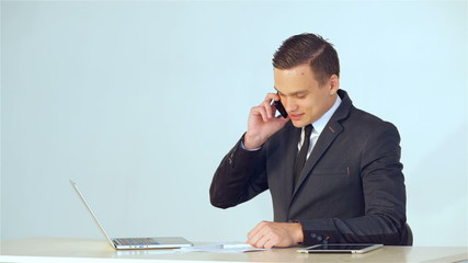 smiling young businessman making a phone call
