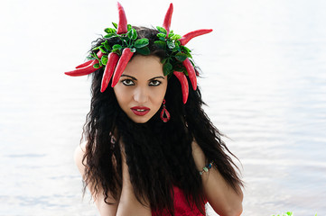 portrait of a beautiful brunette with red pepper on the head