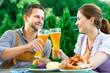 Leinwanddruck Bild - Glückliches Paar im Biergarten in Bayern