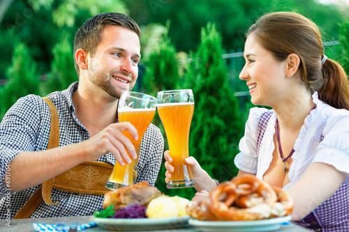 Leinwanddruck Bild Glückliches Paar im Biergarten in Bayern