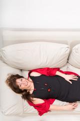 Schöne reife Frau auf der Couch liegend